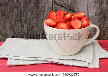 Simple rustic composition with beige ceramic cup decorated with heart shape full of sweet tasty ripe strawberry, fresh natural dessert. Vintage kitchen decor. Romantic style. Red and grey color - stock photo