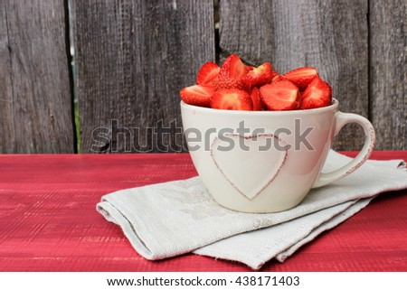 Simple rustic composition with bowl full of sweet tasty ripe strawberry, fresh natural dessert. Vintage kitchen decor. Romantic style. Red and grey color - stock photo