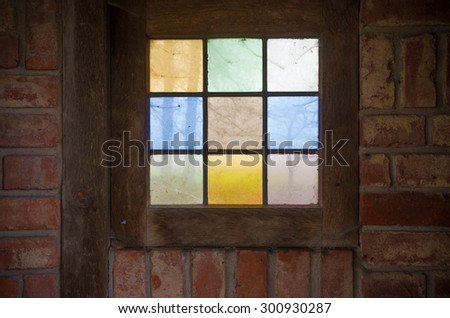 simple stained glass window in a small chapel - stock photo