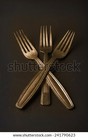 Simple still life of three gold rustic vintage forks - stock photo