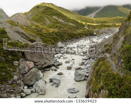 Simple suspension swing bridge crossing a rocky mountain river in Aoraki/ Mount Cook National Park  South Island  New Zealand - stock photo