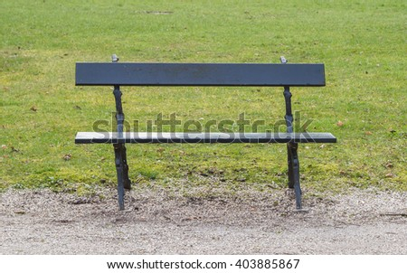 Simple wooden garden bench in a park - stock photo