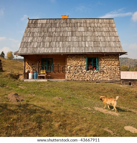 Simple wooden house on hill. Fire wood stacked around the window - stock photo