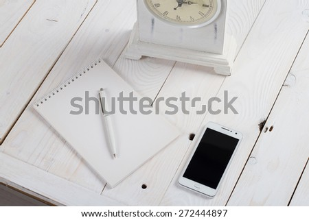 Simple workspace on wooden table on which there is a smartphone and a notebook with a ballpoint pen. Big clock reminded of upcoming cases. - stock photo