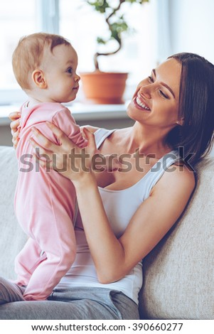 Simply admire her! Cheerful beautiful young woman holding baby girl in her hands and looking at her with love while sitting on the couch at home - stock photo
