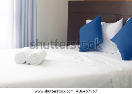 simply modern bedroom decorated with blue pillow and towel roll. - stock photo
