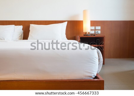 simply white and wood decor bedroom in hotel. - stock photo