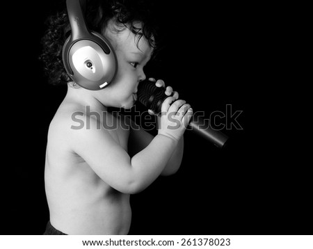 Sing baby with headphone and microphone,isolated on a black background. - stock photo