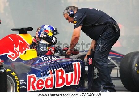 SINGAPORE - APRIL 24: David Coulthard in the Red Bull Racing F1 car RB6 to perform stunts during Red Bull Speed Street Singapore on April 24, 2011 in Singapore. - stock photo