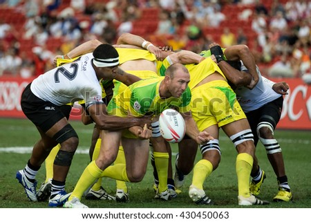SINGAPORE-APRIL 17:Fiji 7s Team (white) plays against Australia 7s team (yellow/green) during Day 2 of HSBC World Rugby Singapore Sevens on April 17, 2016 at National Stadium in Singapore - stock photo
