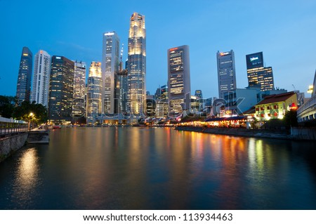 SINGAPORE - APRIL 25: The Singapore skyline shines at night as tourists frequent the riverside shops and restaurants along Boat Quay, Singapore April 25, 2011 in Singapore - stock photo