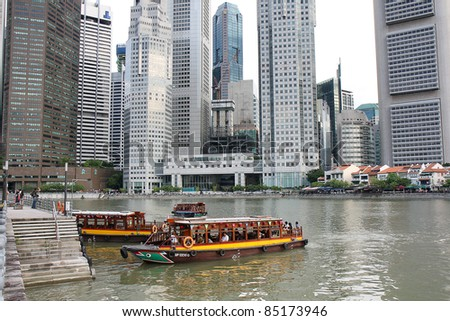 SINGAPORE - AUGUST 21: A tourist boat approaches the Raffles Landing Site, on August 21, 2010 in Singapore. The Singapore River Cruise is a tourist attraction in this former British colony. - stock photo
