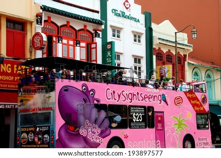 SINGAPORE - December 28, 2007:  A pink City Sightseeing double decker bus with open roof drives tourists past colourful Chinese shops lining South Bridge Road in Chinatown - stock photo