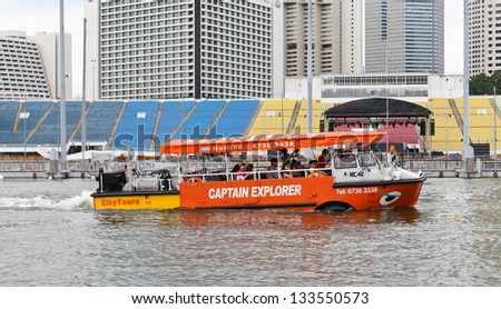 SINGAPORE -DECEMBER 27: A tourist boat moves along the river on December 27, 2012 in Singapore. The Singapore River Cruise is a tourist attraction in this former British colony. - stock photo