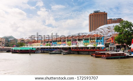 SINGAPORE - DECEMBER 24: Boats docked along the waterfront of Clarke Quay. Photo taken December 24, 2013 in Singapore. - stock photo
