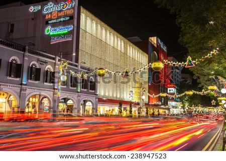 SINGAPORE - DECEMBER 12: Night view of famous festive Orchard Road in Singapore Dec. 12, 2014. Colorful street decorations and motion blur on streaking traffic tail lights during Christmas season. - stock photo