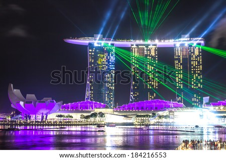SINGAPORE - DECEMBER 15 2013: The Marina Bay Sands Resort Hotel in Singapore displaying a light show at night. Purple lights and green lasers. - stock photo