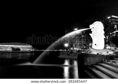 Singapore - February 18: Merlion of Singapore by night, business buildings in the background. The Merlion statue is a symbol of the city, on February 18, 2015 in Singapore - stock photo