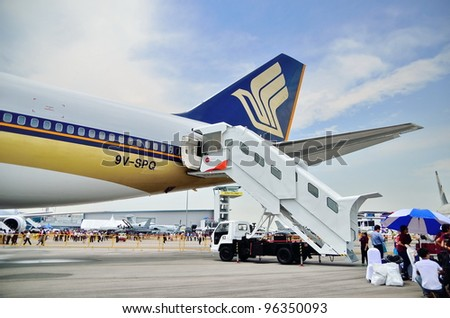 SINGAPORE - FEBRUARY 17: Passenger step connected to Singapore Airlines' (SIA) last Boeing 747-400 at Singapore Airshow on February 17, 2012 in Singapore - stock photo