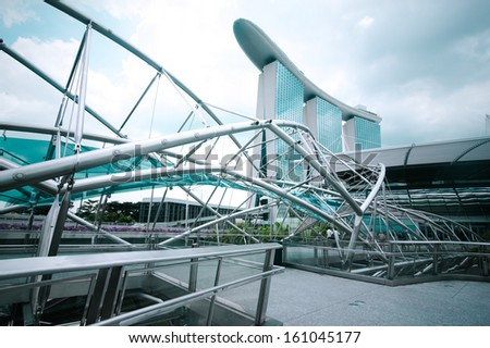 SINGAPORE - FEBRUARY 26: Urban landscape with Marina Bay Sands Hotel and Helix Bridge on Febr 26, 2013. Modern skyscrapers of business district Marina Bay Sands at most financial developing Asian city - stock photo