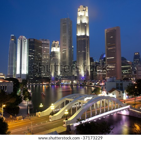 Singapore financial district skyline at night framed by Elgin Bridge and the Singapore River - stock photo