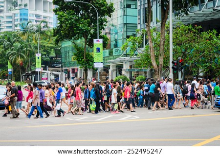 SINGAPORE - 01 JAN 2014: Crowd on pedestrians crossing on famous street Orchard Road in Singapore. Orchard Road is the most popular shopping enclave of Singapore and major tourist attraction. - stock photo