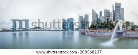SINGAPORE - 1 JAN, 2014: Marina Bay central business district in Singapore. Day time city skyline panorama. Marina Bay Sands and Merlion statue are famous landmarks of the country  - stock photo