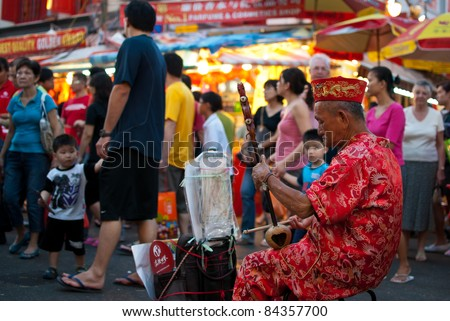 SINGAPORE - JANUARY 30: Elder street musician busking along a busy street during Chinese New Year taken on January 30, 2010 in Singapore. - stock photo