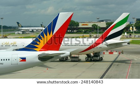 SINGAPORE - JANUARY 10:  Tails of Emirate Boeing 777-300ER and Philippines Airlines Airbus 330 at Changi Airport on January 10, 2015 in Singapore - stock photo