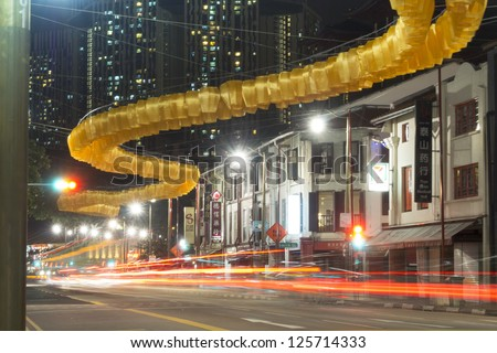 SINGAPORE - JANUARY 12: Yellow lanterns garland hanged over South Bridge Road just before Chinese New Year Celebration in Chinatown district of Singapore on January 12,  2013 in Singapore. - stock photo
