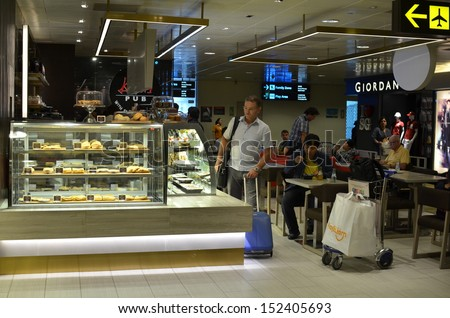 SINGAPORE-JULY 31: Passengers buy some food before take off on July 31, 2013 in Changi Airport, Singapore. Singapore airport provides the best shopping experience to the passengers.  - stock photo