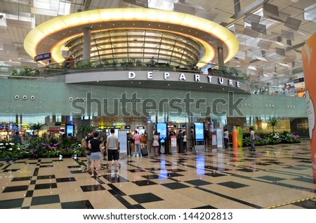 SINGAPORE-JUNE 14: Passengers leave via departure hall in Terminal 3 in Changi Airport, Singapore on June 14, 2013. Singapore airport is the main aviation hub in South East Asia. - stock photo
