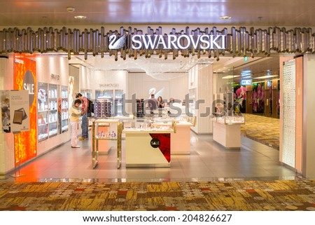 SINGAPORE - JUNE 20: Swarovski store in Terminal 3 in Changi Airport, Singapore on June 20, 2014. Swarovski is an Austrian producer of luxury cut lead glass (crystal). - stock photo