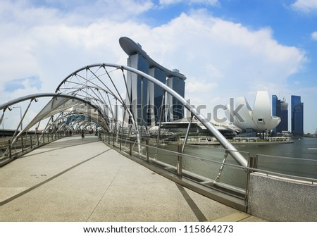 SINGAPORE - JUNE 3: The Marina Bay Sands resort and Helix Bridge on June 3, 2011 in Singapore. The integrated resort in Singapore is the world's most expensive casino property. - stock photo