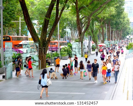 SINGAPORE - MARCH 8: Pedestrians walk along famous Orchard road on March 8, 2013 in Singapore. This 2.2 kilometre street is the retail and entertainment hub of Singapore and major tourist attraction. - stock photo