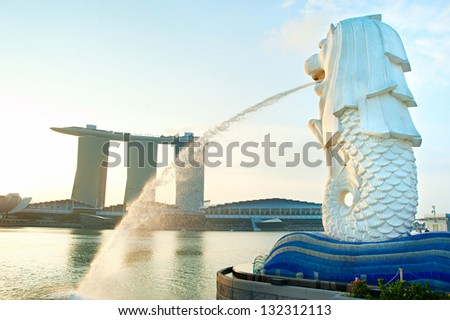 SINGAPORE - MARCH 08: The Merlion fountain in front of the Marina Bay Sands hotel on March 08, 2013 in Singapore. Merlion is a imaginary creature with the head of a lion, seen as a symbol of Singapore - stock photo