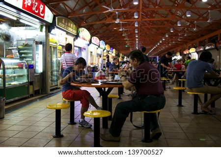 SINGAPORE - MAY 5 - Locals eat at a popular food hall on May 5, 2013 in Chinatown, Singapore.  Inexpensive food stalls are numerous in the city so most Singaporeans dine out at least once a day. - stock photo