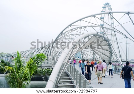 SINGAPORE - MAY 02: The Helix Bridge on  May 02, 2011 in Singapore. Is a bridge in the Marina Bay. The Helix is fabricated from 650 tonnes of Duplex Stainless Steel and 1000 tonnes of carbon steel. - stock photo