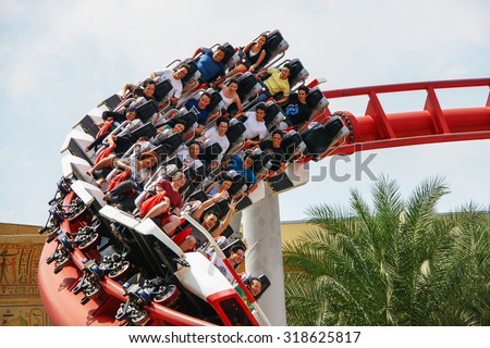 SINGAPORE - MAY 7: Unidentified people having fun at a roller coaster's loop with gloomy sky due to haze at UNIVERSAL STUDIOS SINGAPORE at Singapore Resorts World Sentosa on May 7, 2011. - stock photo