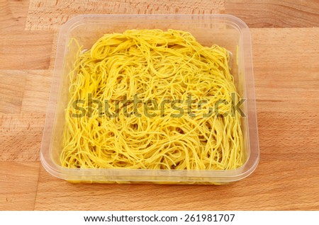 Singapore noodles in a plastic tray on a wooden board - stock photo