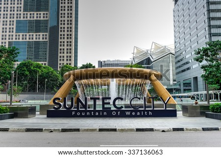 SINGAPORE â?? NOV 7, 2015: Front view of Fountain of Wealth at Suntect City - the largest fountain in the world, like a golden ring in the palm of hand, designs by Tsao & McKown, emphasis on feng shui - stock photo