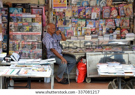 SINGAPORE - NOV 07, 2015: Owner of Indian magazines store along at the roadside of Little India in Singapore - stock photo
