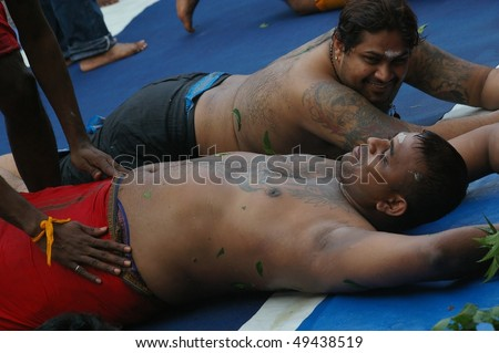 SINGAPORE - NOVEMBER 04: Hindus doing ritual rolling at Sri Mariamman Temple for the Thimithi Festival  November 04, 2009 in Singapore. - stock photo