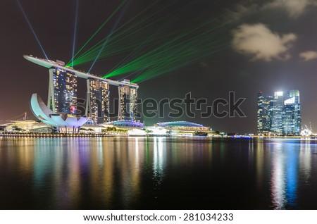 SINGAPORE-OCT 06 , 2014 : Singapore skyline of marina bay in Singapore at night and laser show at marina bay sands hotel  - stock photo