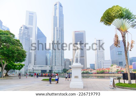 "SINGAPORE-OCT 19, 2014:Statue of Sir Tomas Stamford Raffles  with modern skyscrapers  background-best known for his founding of the city of Singapore.He is often described as the""Father of Singapore"". - stock photo"