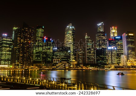 SINGAPORE - OCTOBER 3: Singapore's financial district illuminates the night sky on Oct. 3, 2012. The Marina Bay area contains the core financial and commercial districts of the island-state.  - stock photo