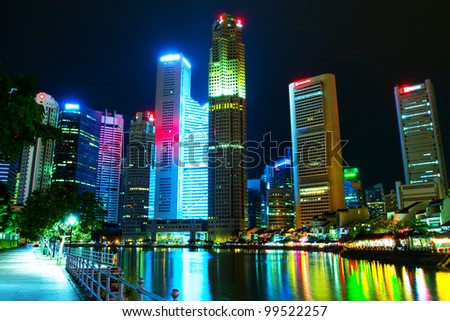 Singapore's downtown skyscrapers reflected on water at night  (Night panorama of the city in the artificial lighting) - stock photo