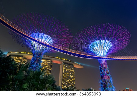SINGAPORE/SINGAPORE -DEC 23, 2015: Night view of Super tree Grove at Gardens by the Bay and Marina Bay Sands hotel. Night view of Super tree Grove walk and Marina Bay Sands hotel, Singapore - stock photo