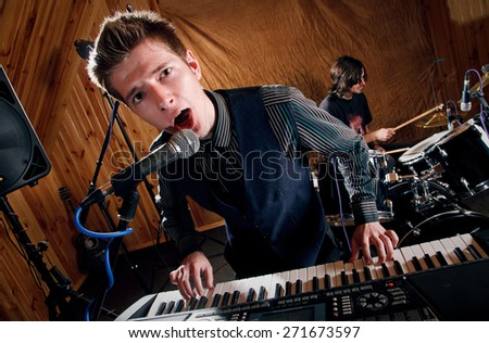 singer keyboard player sings into a microphone - stock photo