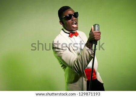 Singing black american man in suit wearing sunglasses. Vintage. - stock photo